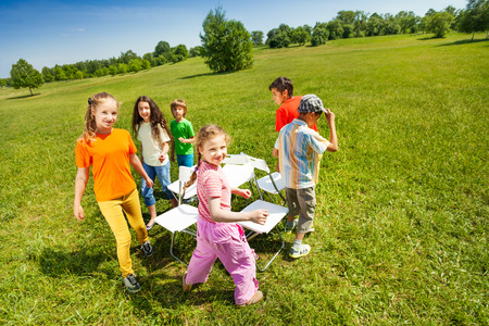 round chairs: Children go around playing musical chairs outside Stock Photo