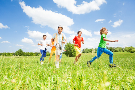 playing field: Excited kids playing and running in the field Stock Photo