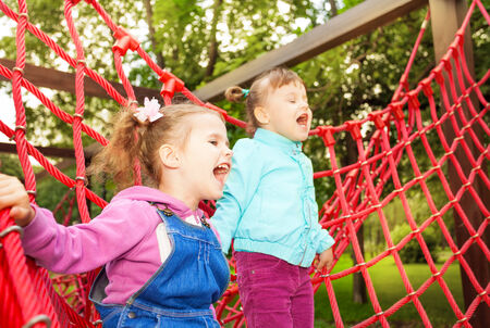 meshwork: Girls screaming and standing on net of playground