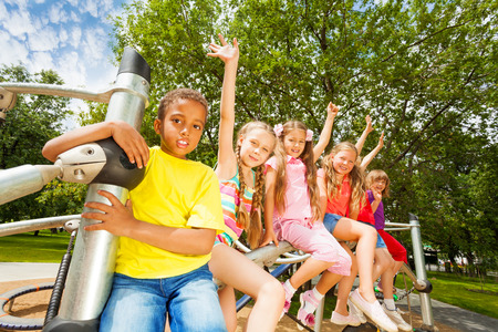 waive: Children waiving hands sitting on round bar Stock Photo