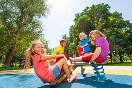 playground ride: Children sit on playground carousel with springs Stock Photo