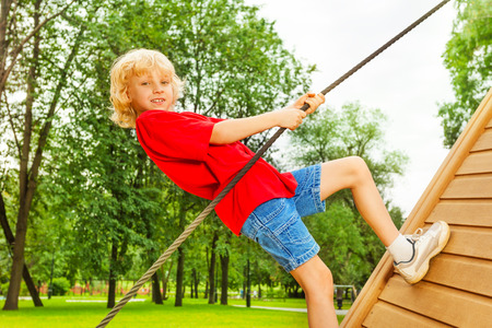 eight years old: Boy holds rope and climbs on wooden construction