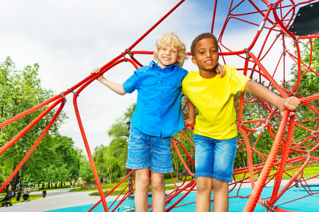eight years old: Two diverse looking boys stand close on red web Stock Photo