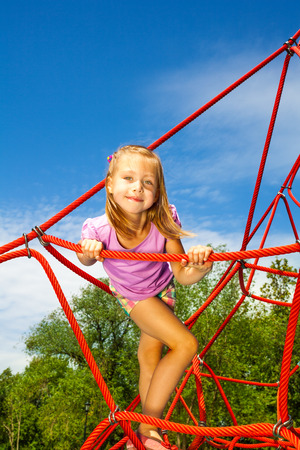 Cute girl holds rope and stands on it in park photo