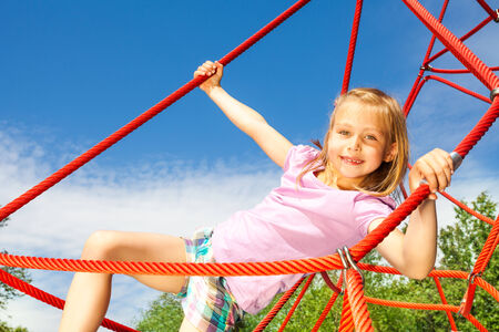 Girl hangs on red net ropes with two arms photo