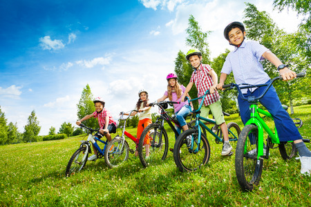 Row of children in colorful helmets holding bikes