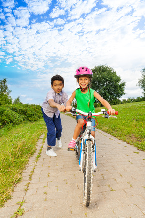 Boy helps girl to ride bike and holds handle-bar photo