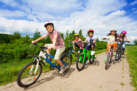 Kids in helmets riding bikes together Stock Photo