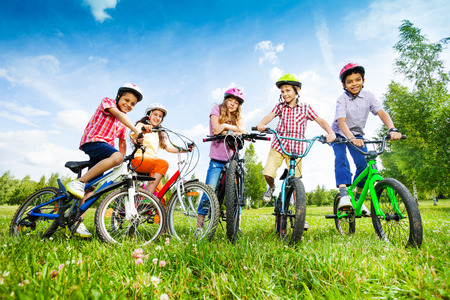 Children in colorful helmets hold their bikes Фото со стока - 30721233
