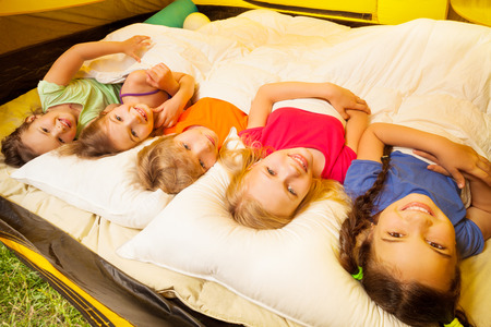 Five pretty kids lay covered with blanket photo