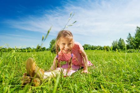 splitting up: Happy girl making leg-split on grass in summer
