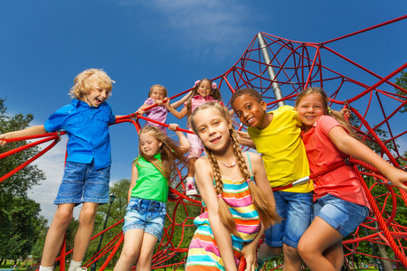 seven years: Many kids stand on red ropes together in park Stock Photo