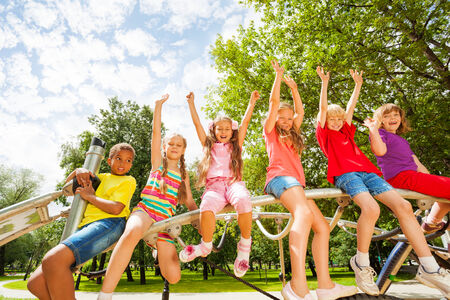 waive: Children on round bar of playground construction