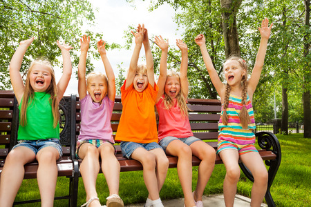 Happy children with arms and sit in row on bench Stock fotó
