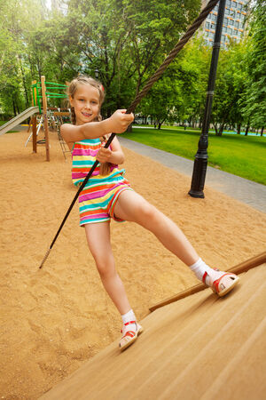 Girl tries to climb on wooden construction photo