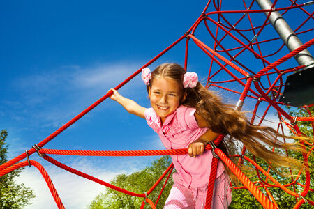 Smiling girl with long hair stands on red rope photo