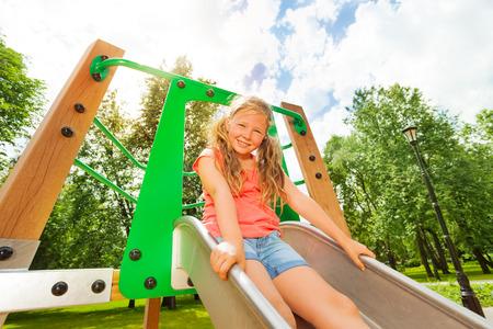 Funny girl on children chute ready to slide photo