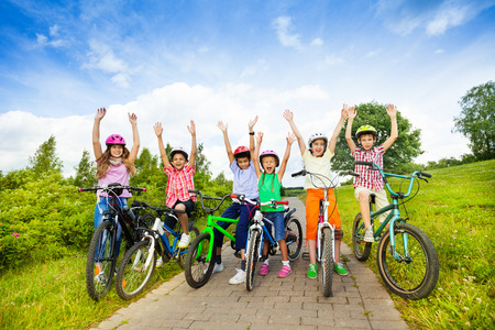Excited kids in helmets on bikes with hands up
