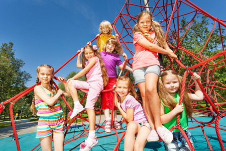 eight years old: Smiling group of children sit on red ropes