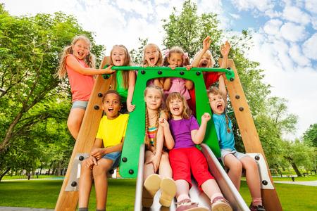 Grappige kinderen op speelplaats chute met armen omhoog