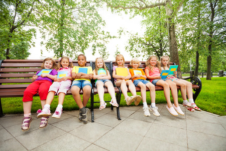 eight years old: Children sitting in a row on bench with notebooks