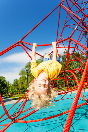 upside down: Smiling boy hangs upside down on rope of red net Stock Photo