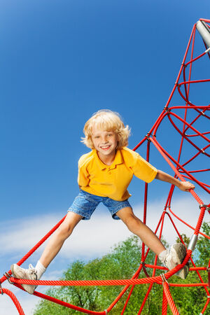 meshwork: Active boy stands on red rope with legs apart Stock Photo
