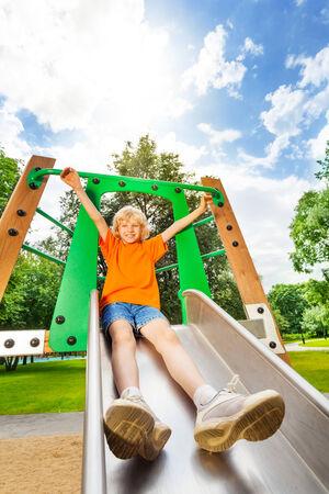 Boy sliding on metallic chute with hands up photo