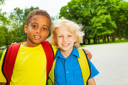 7 years old: Portrait of two boys hugging on shoulders Stock Photo