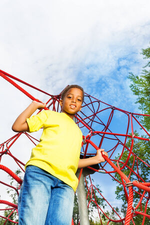 kids holding hands: African boy holds and stands on red ropes Stock Photo