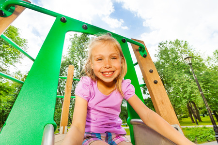 Portrait of funny girl on playground chute photo