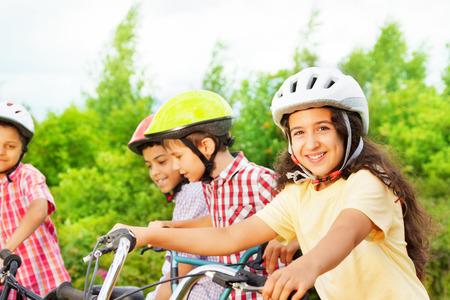 handlebar: Small cute girl in helmet holds bike handle-bar