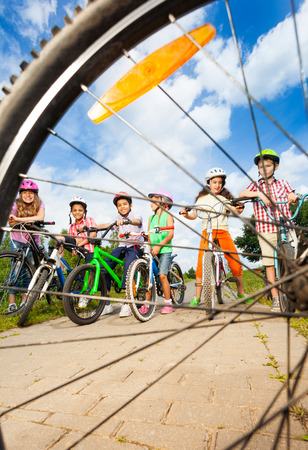 view through: Kids with helmets hold bikes view through spoke