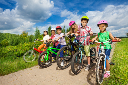 multinational: Children in row wearing helmets holding bikes Stock Photo
