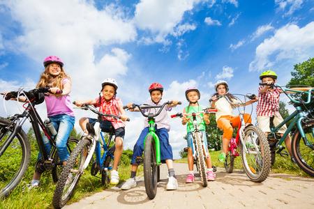 niños en bicicleta: Debajo de la opinión de ángulo de niños en cascos con bicicletas
