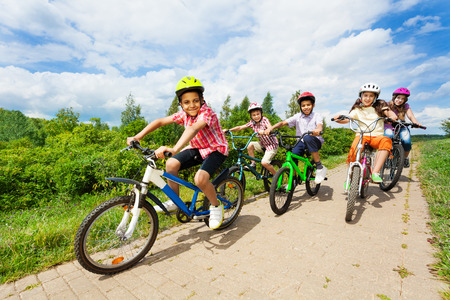 bicycle race: Happy kids riding bikes like in race together Stock Photo