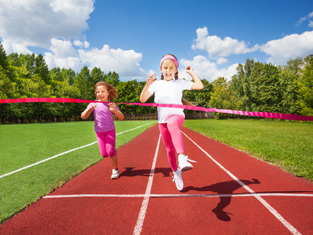 running track: Girl runs and reaches ribbon excited to win  Stock Photo