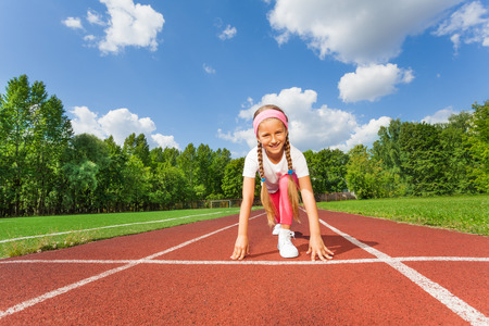 knee bend: Girl in ready position on bend knee to run Stock Photo