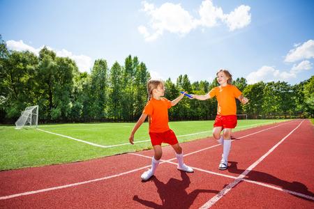 carrera de relevos: Muchacha corriente con el bastón se lo da a otro corredor
