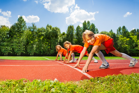 sports uniform: Three smiling children in ready position to run Stock Photo