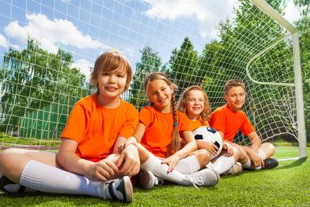 Happy children sitting together on field grass photo