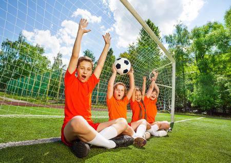 Opgewonden kinderen zitten in rij met voetbal en armen omhoog