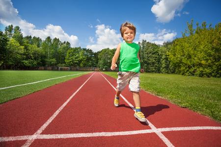 slowly: Cute small boy runs slowly on the marathon road
