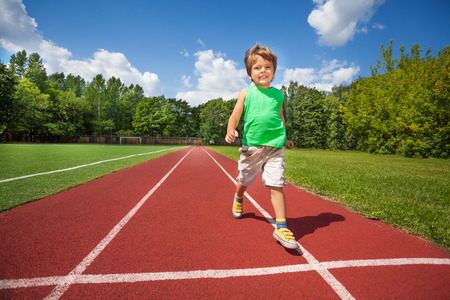 slowly: Pequeño muchacho lindo que se ejecuta con lentitud en el camino del maratón