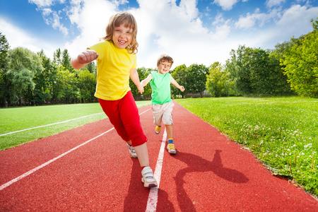 pista de atletismo: Dos niños de la mano corriendo juntos Foto de archivo