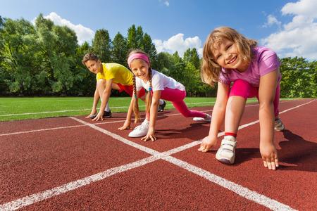 pista de atletismo: Tres niños sonrientes en posición de listo para funcionar Foto de archivo