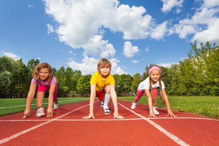 pista de atletismo: Niños sonrientes en las rodillas doblado listos para funcionar