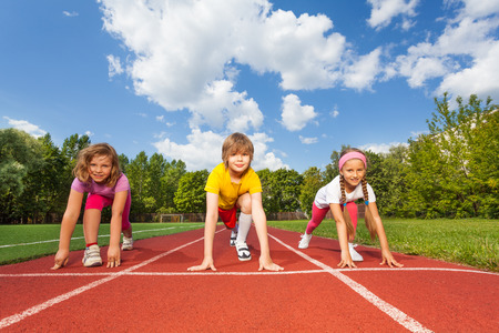 jogging track: Smiling children on bending knees ready to run  Stock Photo
