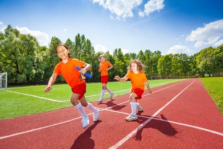 carrera de relevos: Tres muchachas con un rel� batuta funcionamiento Foto de archivo