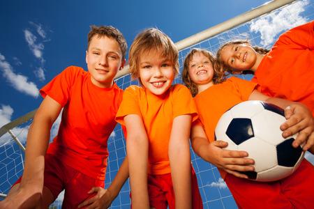 Vier gelukkig kinderen met voetbal portret Stockfoto